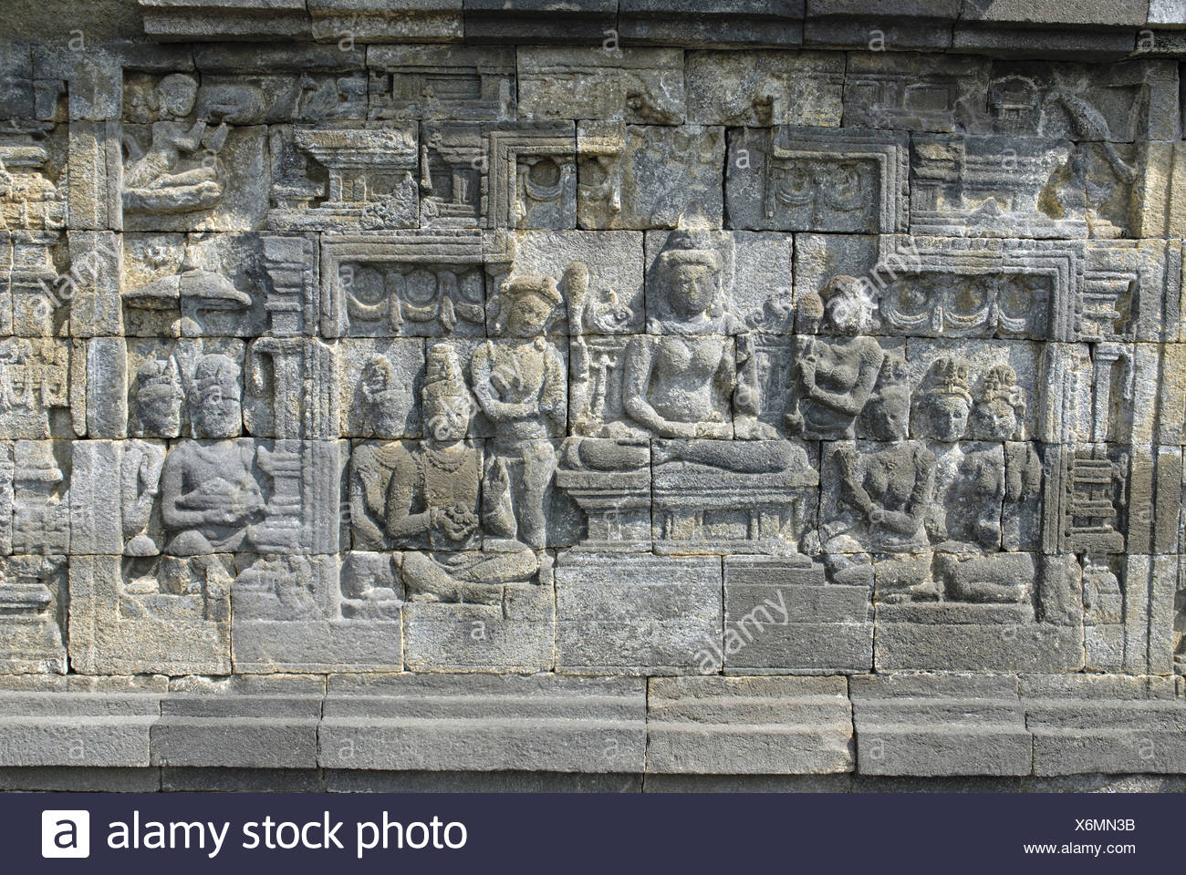 Indonesia-Java-Borobudur, Goddess seated on lotus throne with attendants and  Devotees, closer-view. - Stock Image