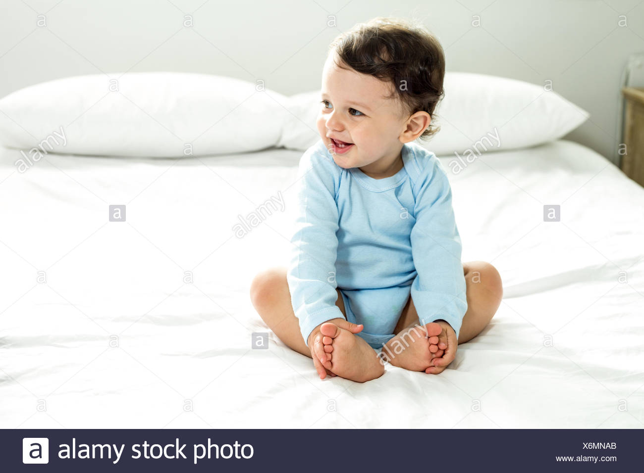 Baby boy smiling while sitting on bed at home - Stock Image