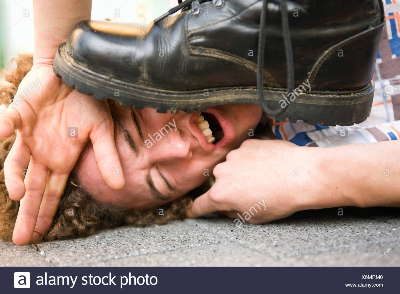 Young man lying on ground being stepped on by someone wearing black boot - Stock Image