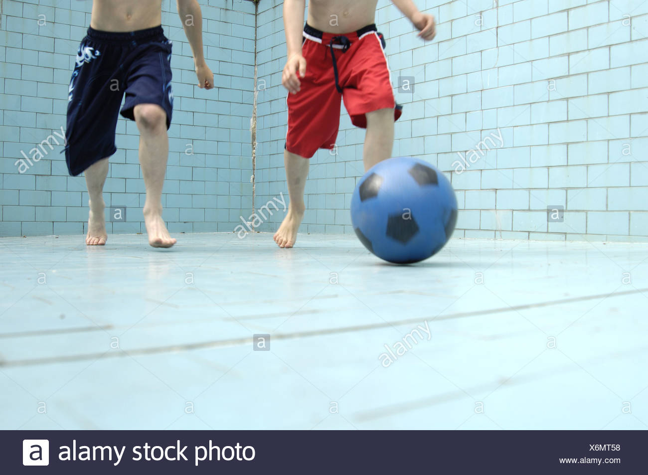 Pool empty children soccer games detail legs series people boys bath-clothing pools basin-ground tiles ball ball-game activity - Stock Image
