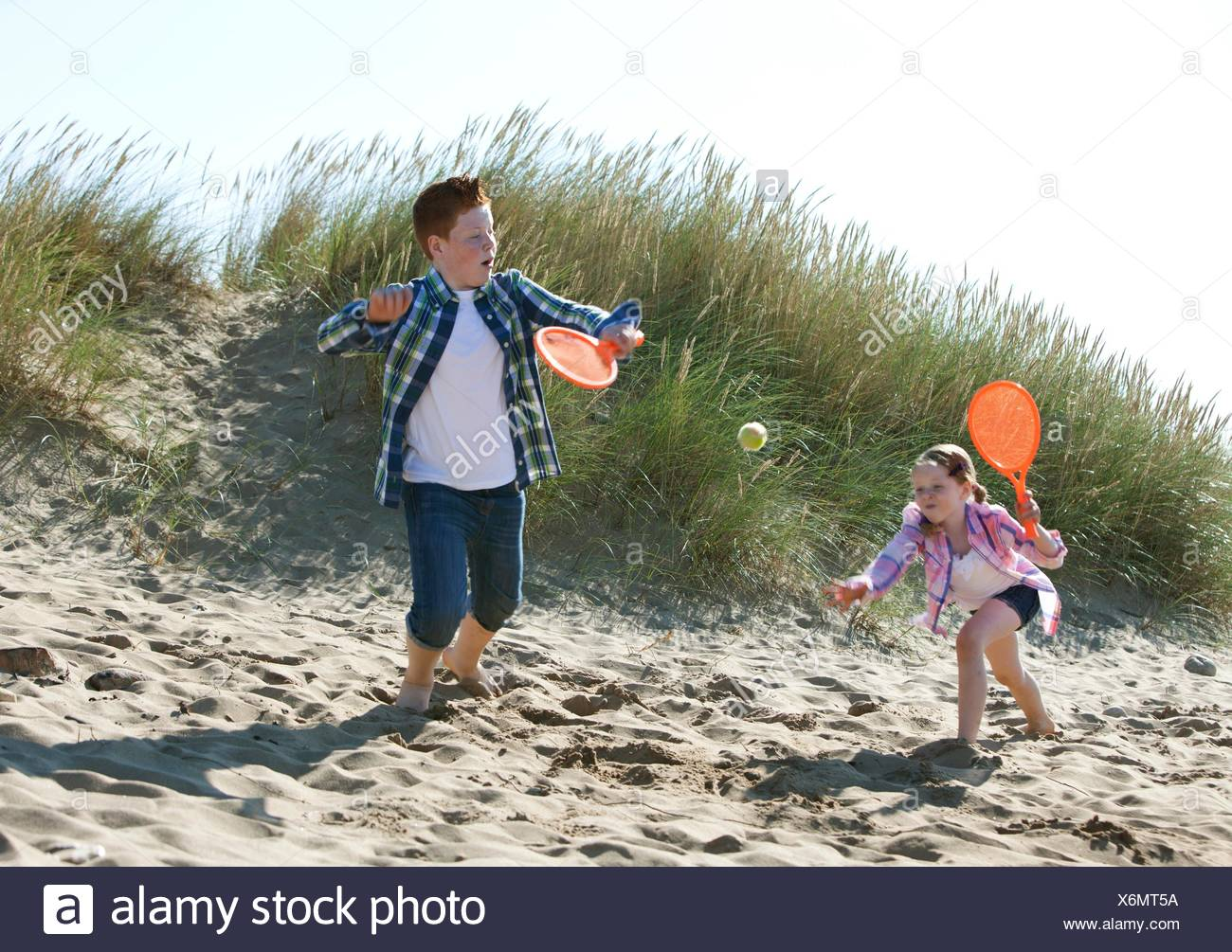 Girl and boy playing with orange sports bat and tennis ball on dunes - Stock Image