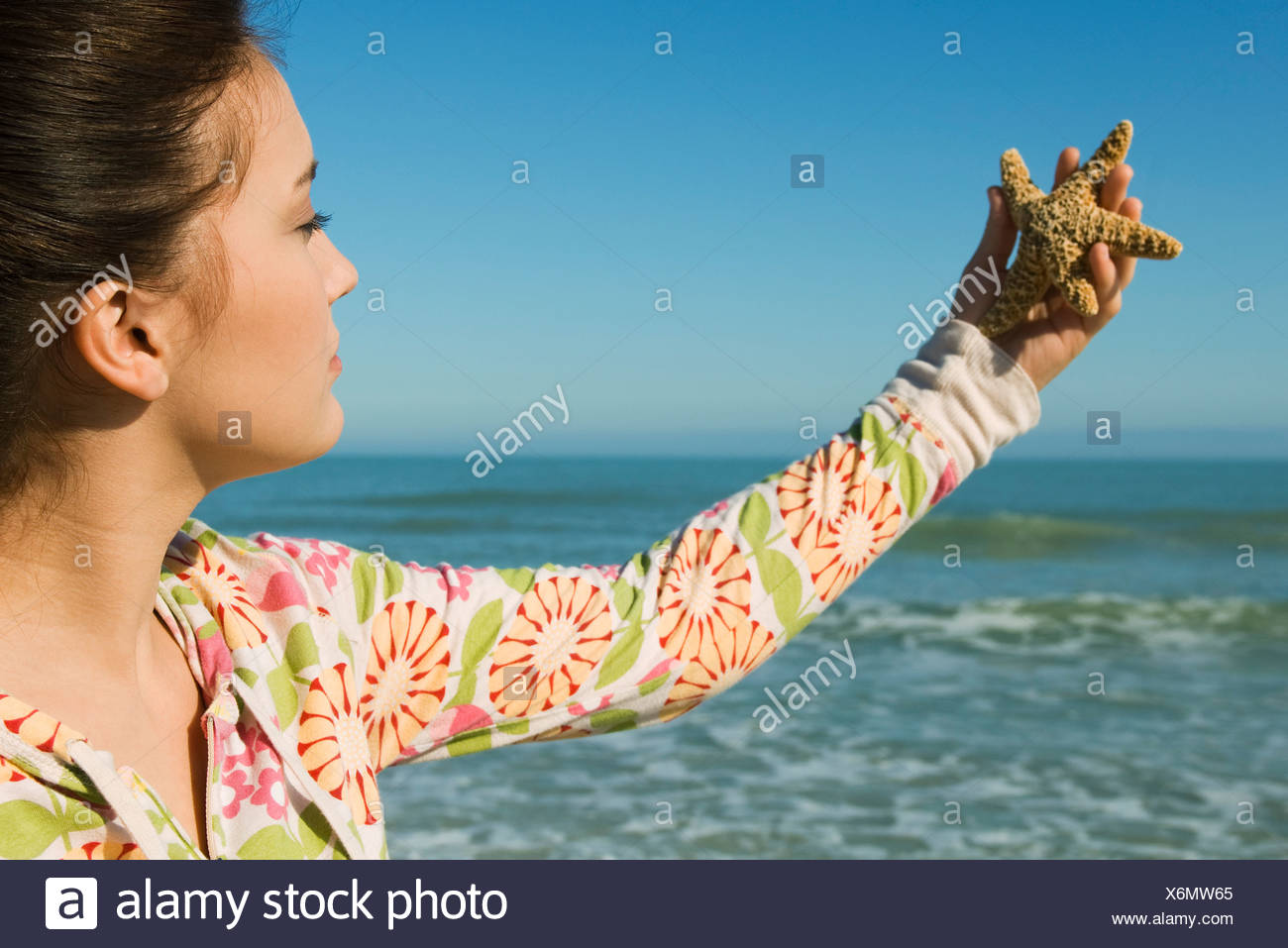 Teenage girl holding out starfish at the beach - Stock Image