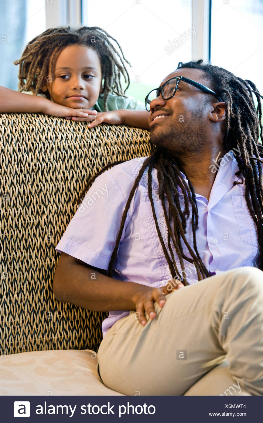 Jamaican father and young son with dreadlocks on sunroom on sofa - Stock Image