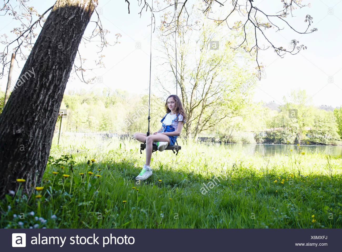 Girl on swing in tree, portrait Stock Photo