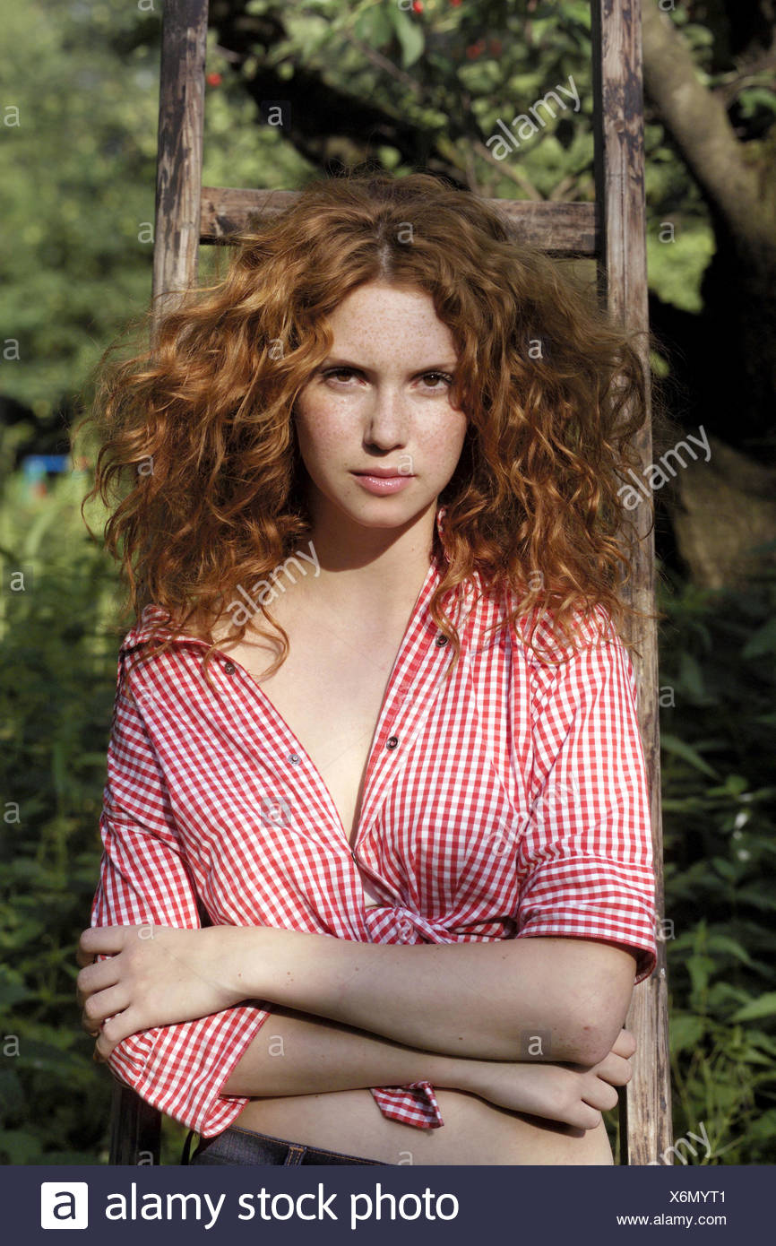 Conductors, woman, seriously, red-haired, curls, lean, half portrait, garden, wooden conductors, lean, redheads, young, long-haired, doubtful, scepticism, self-confidence, self-confidently, women's portrait, freckles, arms crossed, outside - Stock Image