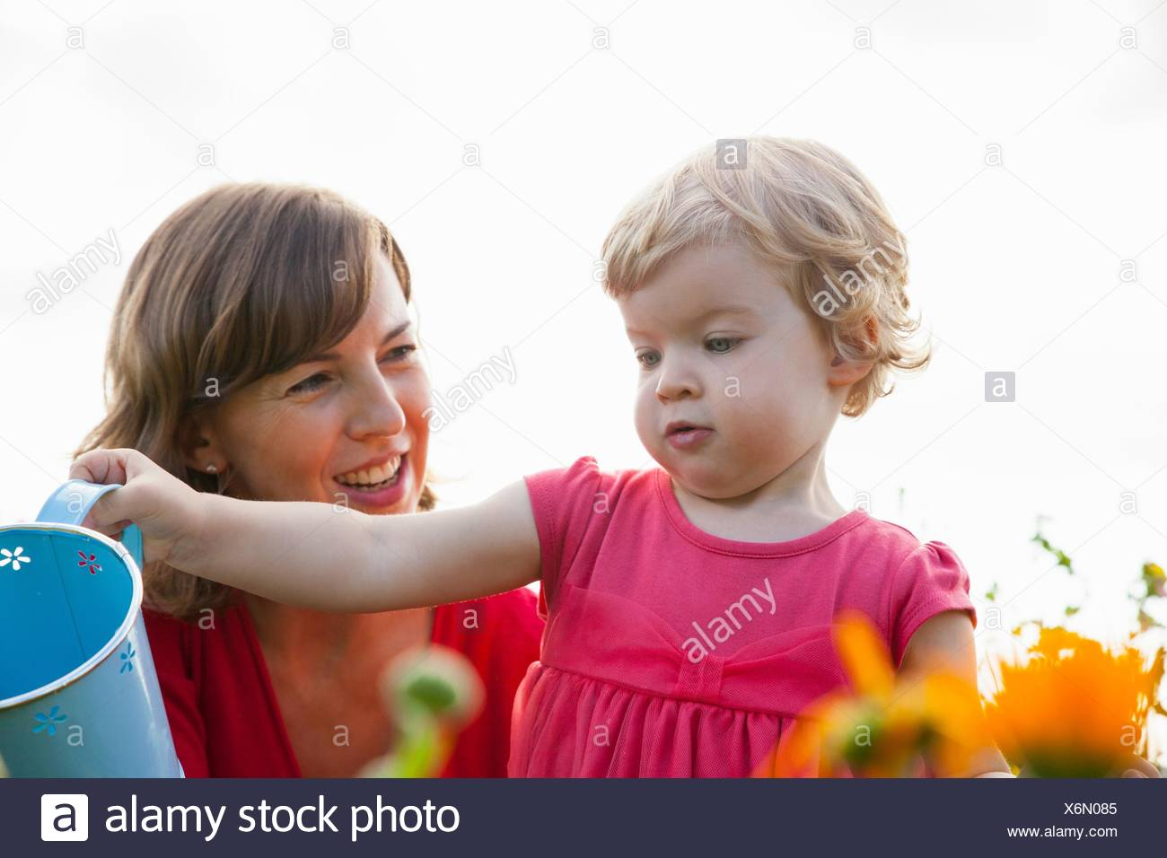 Mid adult mother and toddler daughter watering flowers in field - Stock Image