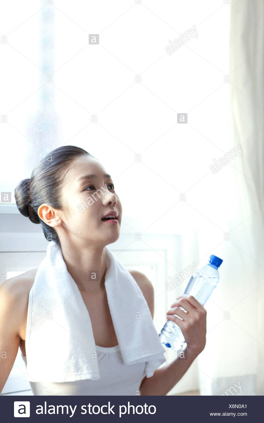 Asian Woman Holding Water Bottle - Stock Image