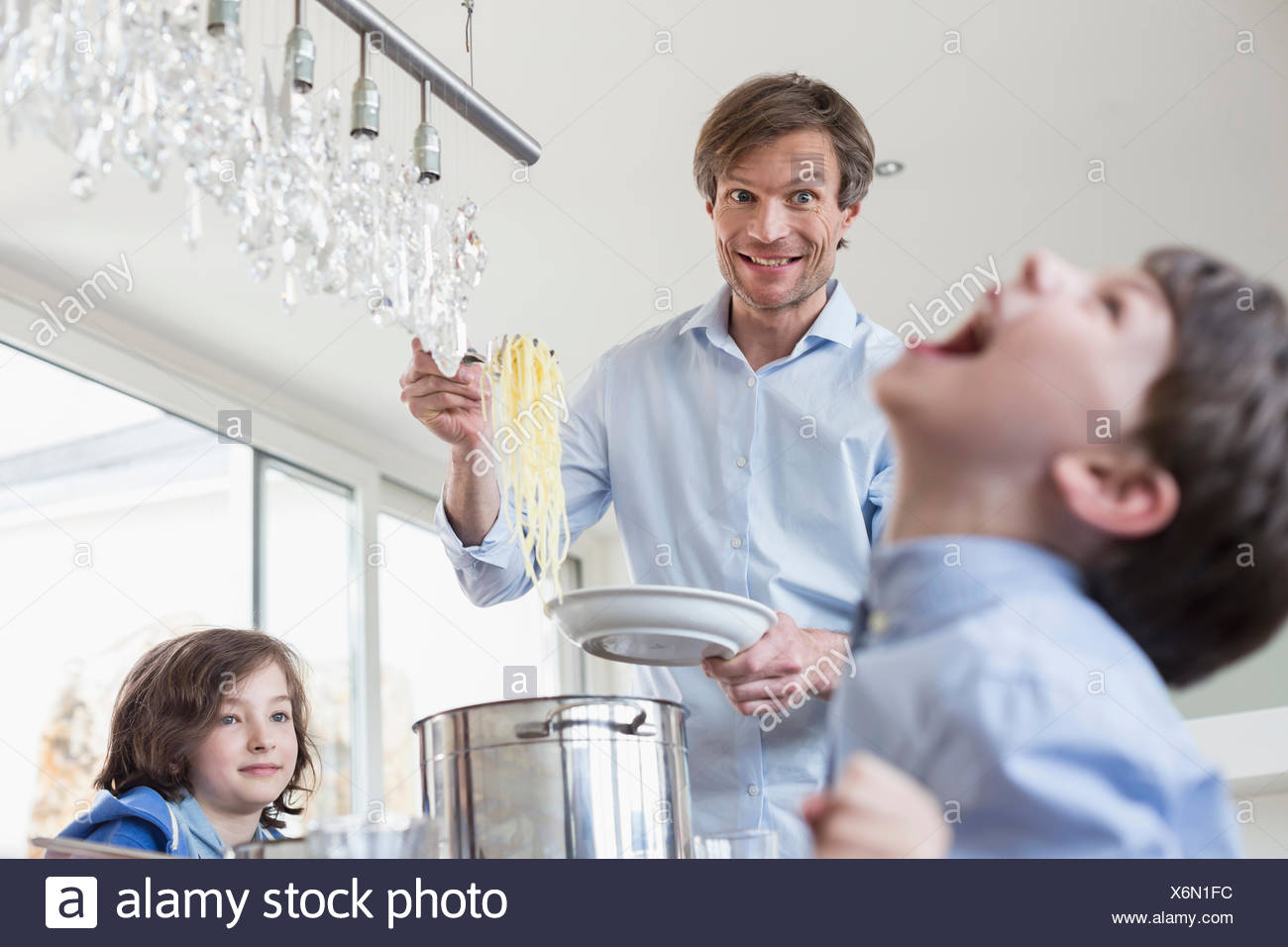 Father hand overing meal to childrens - Stock Image