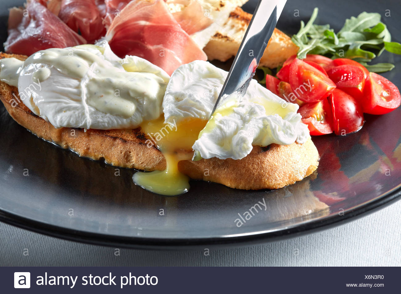 Eggs Benedict on toasted with ham and sauce - Stock Image