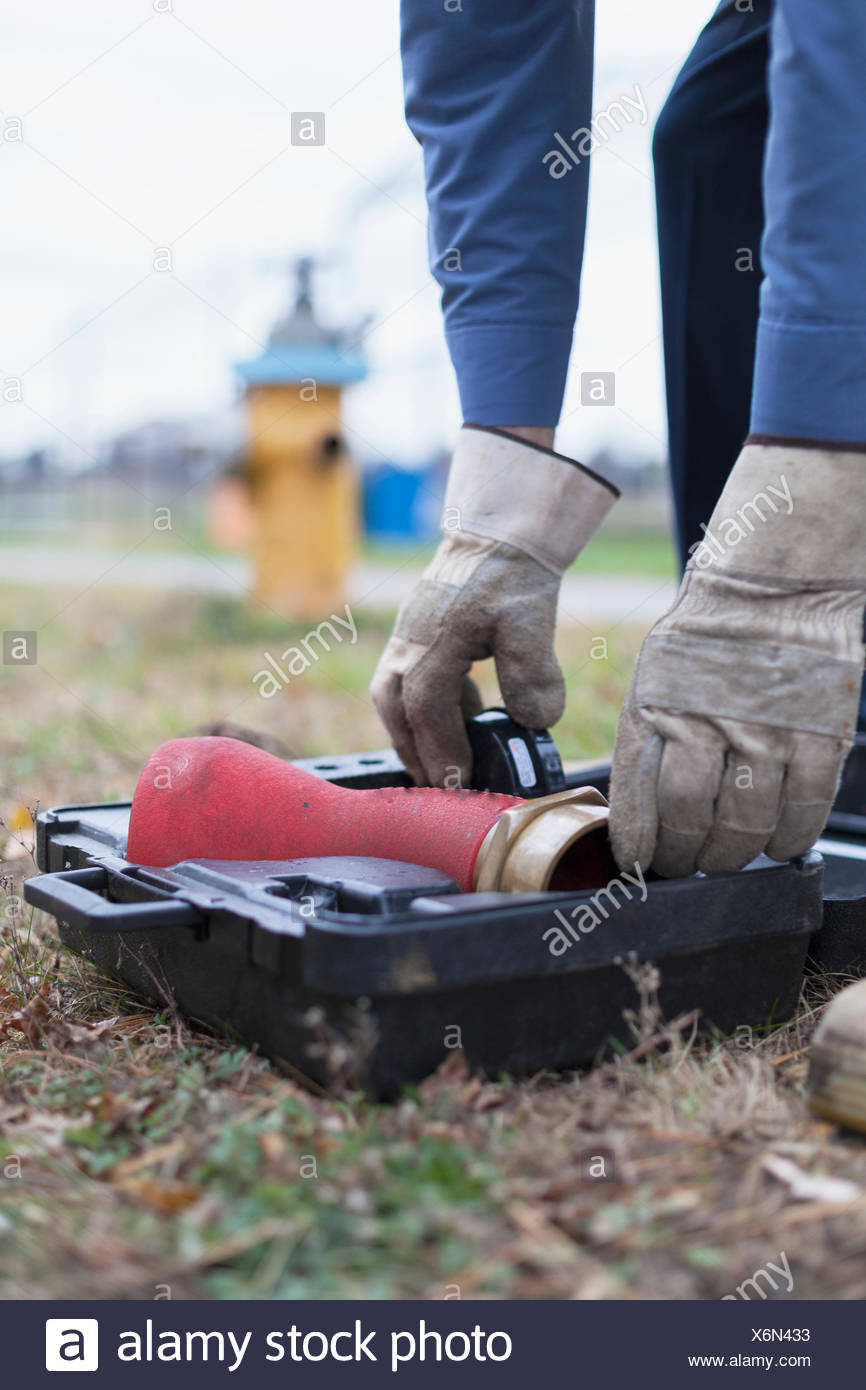 Technician preparing to use hydrant attachment with sensor for flushing mains - Stock Image