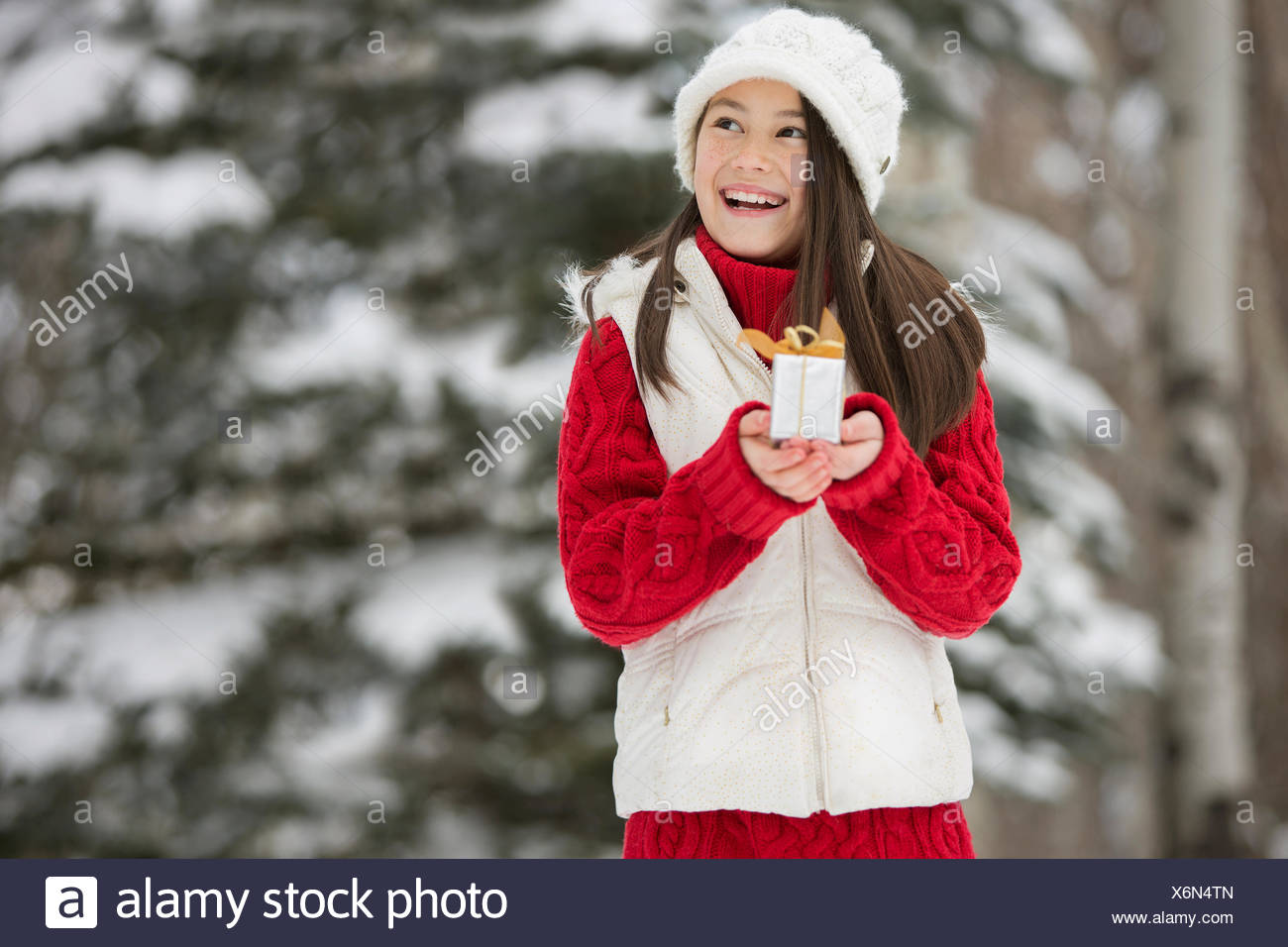 Smiling girl holding small Christmas gift in snow - Stock Image