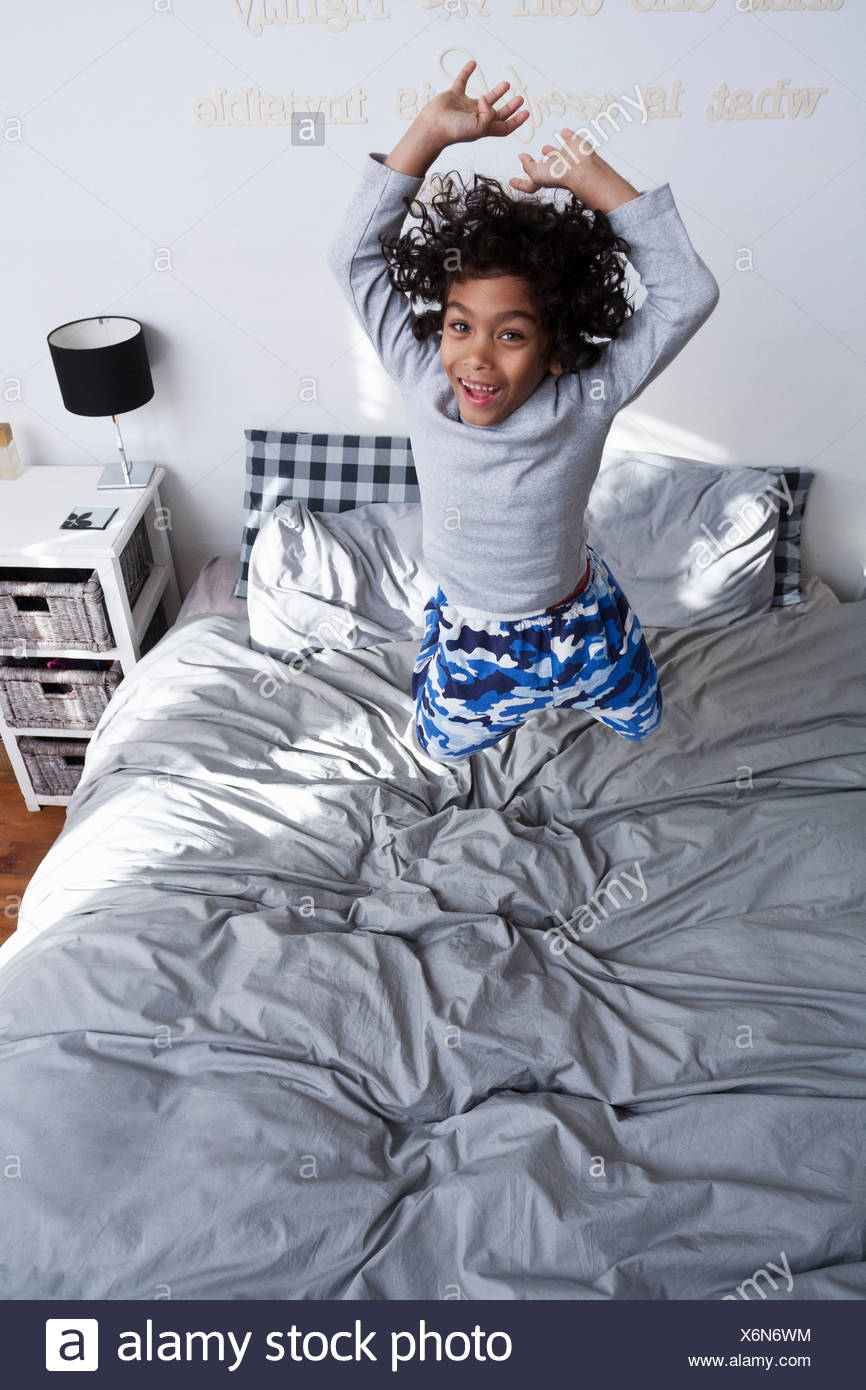Boy jumping on bed with arms up - Stock Image