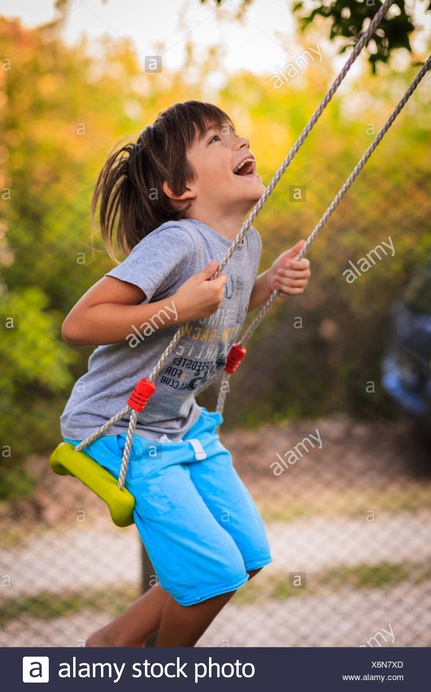 Boy laughing and swinging on a swing - Stock Image