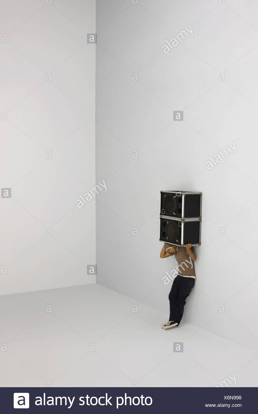 Man carrying two speakers on his shoulders - Stock Image