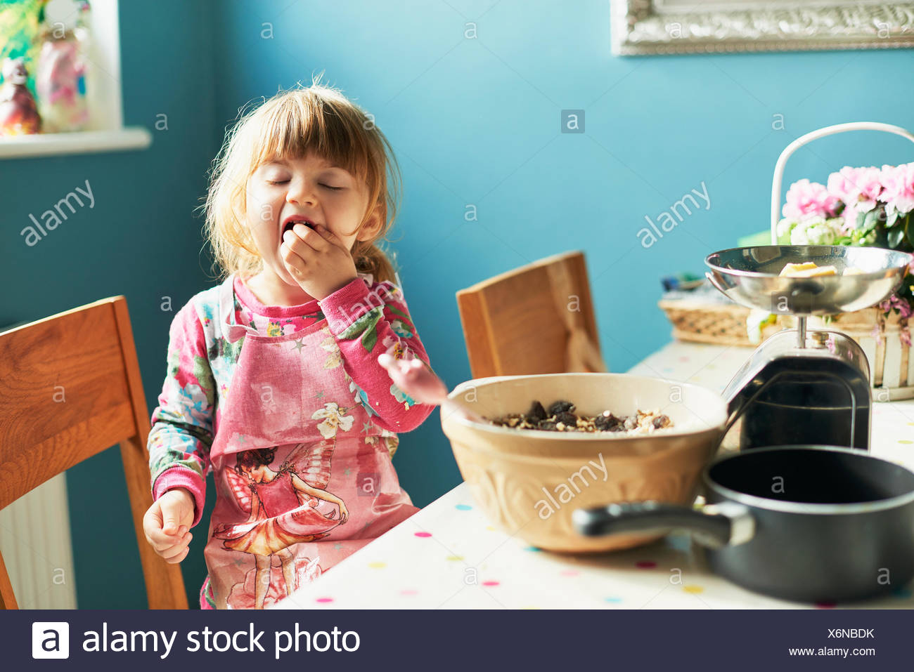 Girl tasting baking ingredients in kitchen - Stock Image