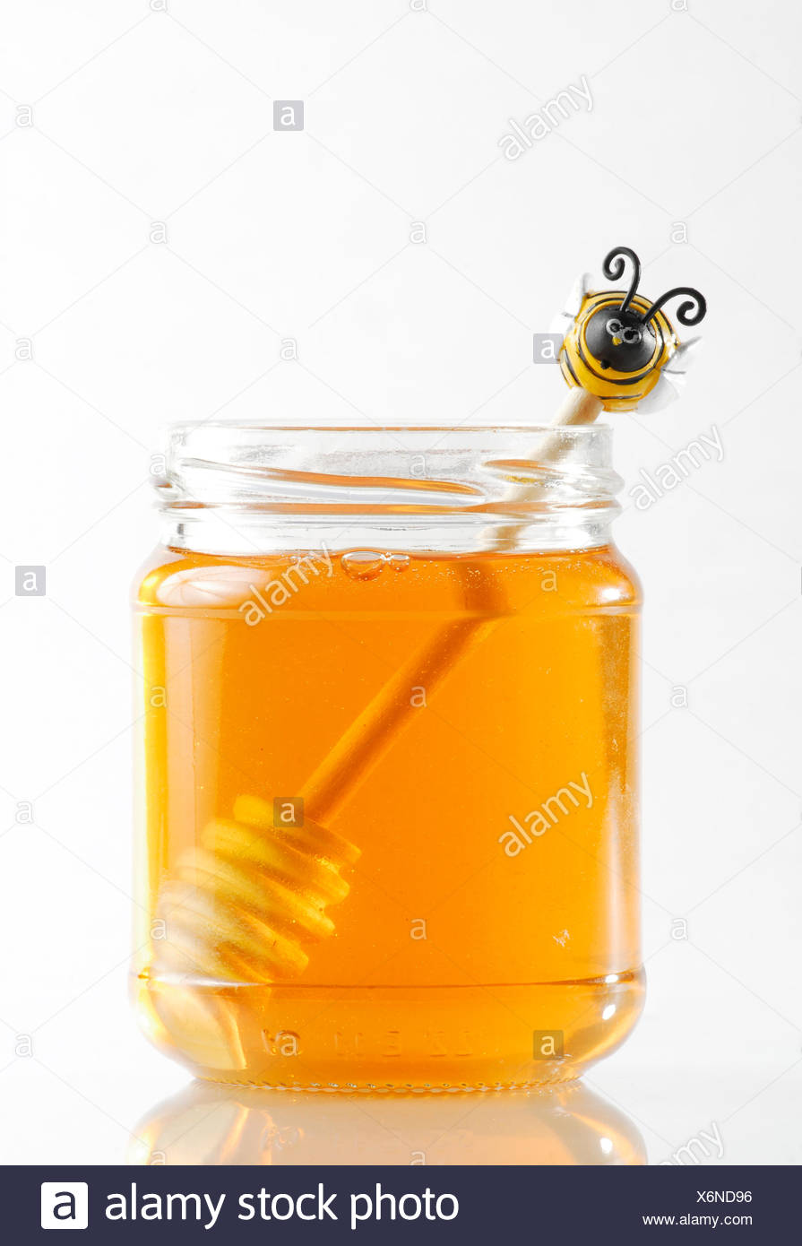 Honey jar with honey spoon - Stock Image