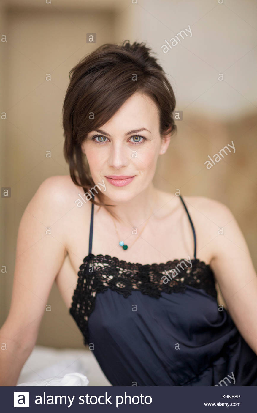 Portrait of a beautiful woman sitting on the bed - Stock Image