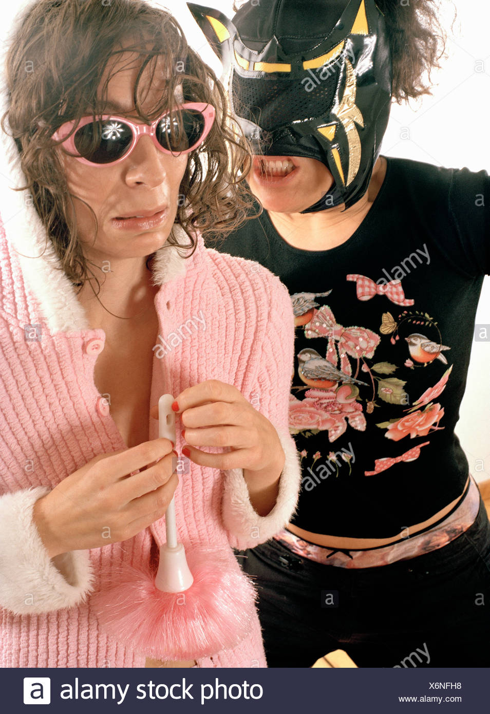 A woman wearing a wrestling mask growling at a woman in a nightgown - Stock Image
