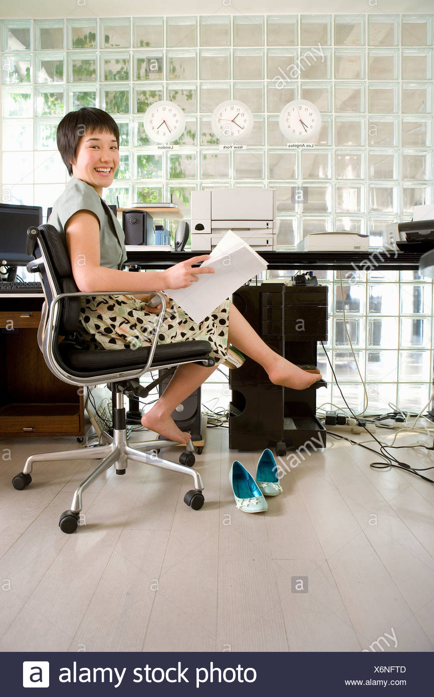 Young barefooted woman sitting in office, holding paperwork, smiling, portrait - Stock Image