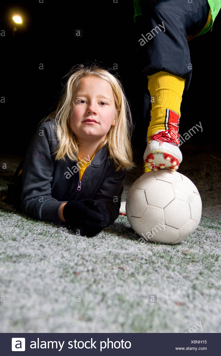 Portrait of a girl lying besides leg of a football - Stock Image