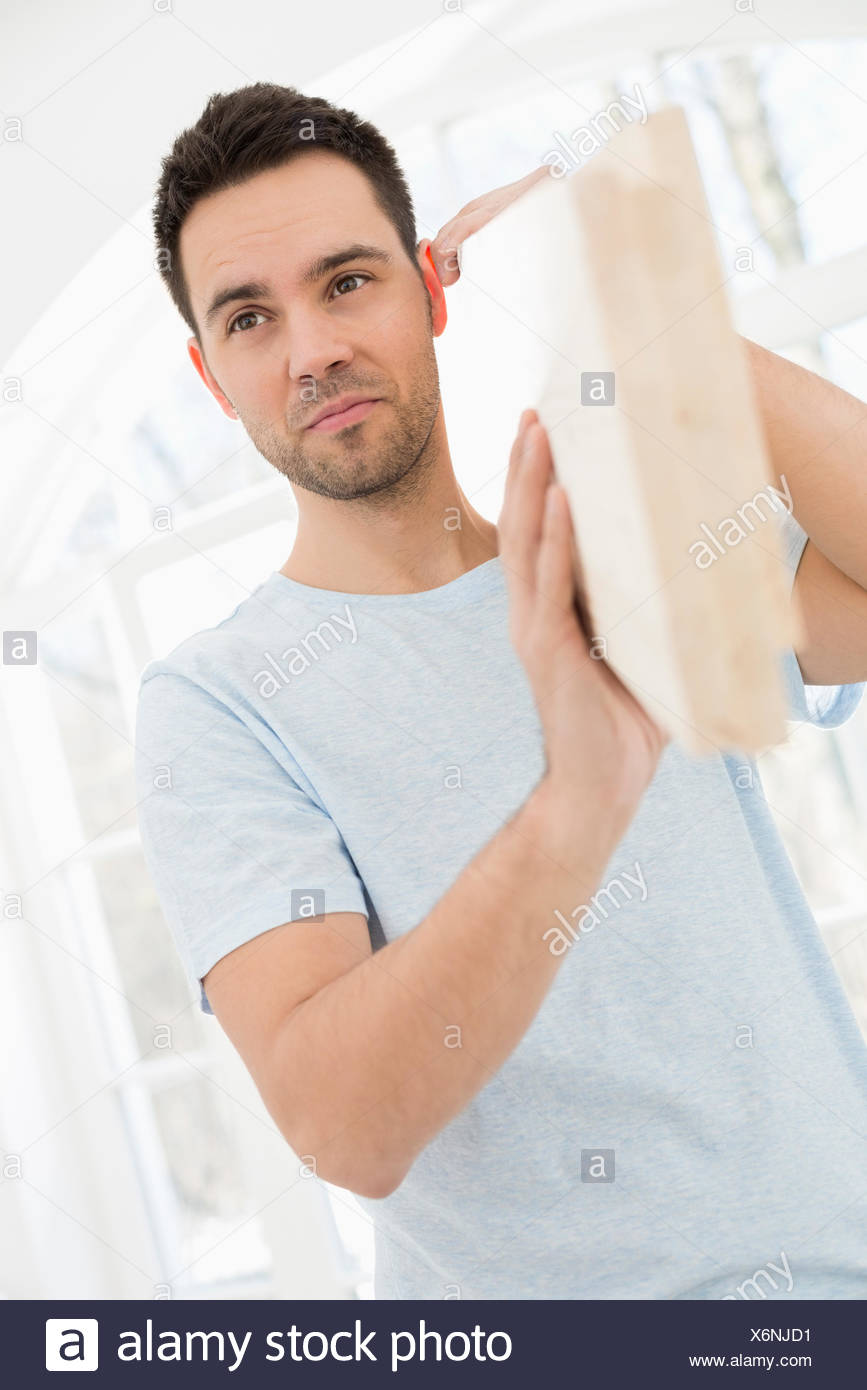 Mid-adult man carrying wooden plank on shoulder Stock Photo