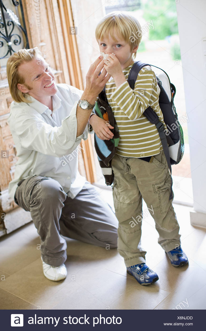 father getting his son ready for school - Stock Image