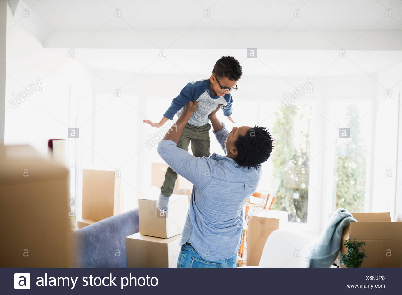 Moving boxes surrounding father lifting son - Stock Image