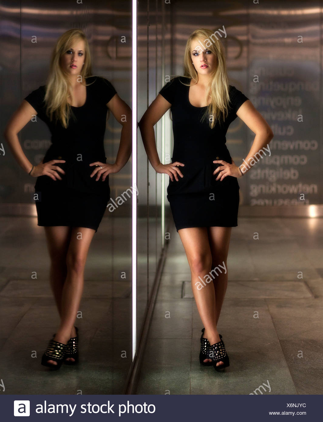 Young woman with long blonde hair wearing a black dress posing in front of glass wall, reflection, mirror image Stock Photo