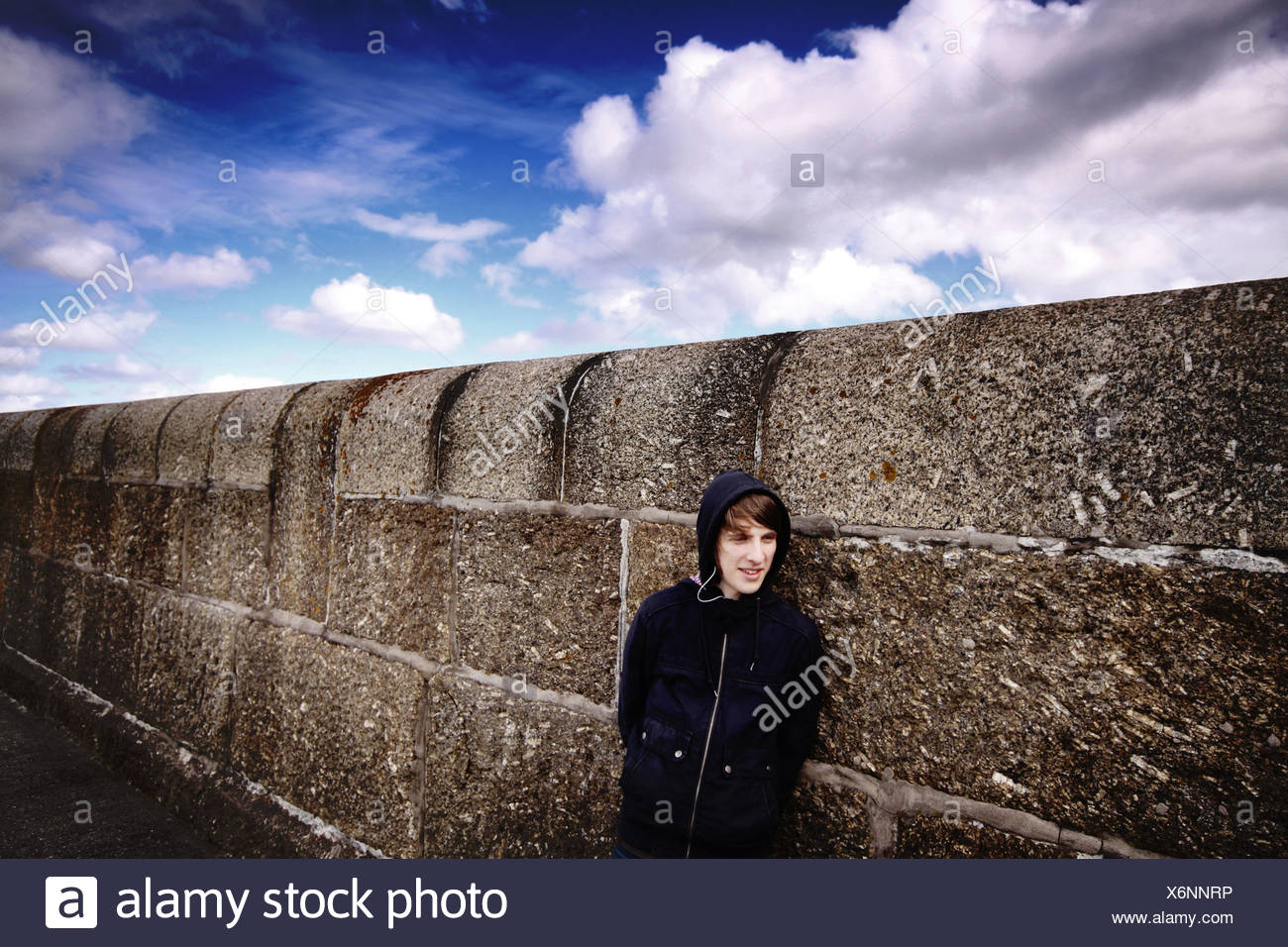 teenager leaning against a wall - Stock Image