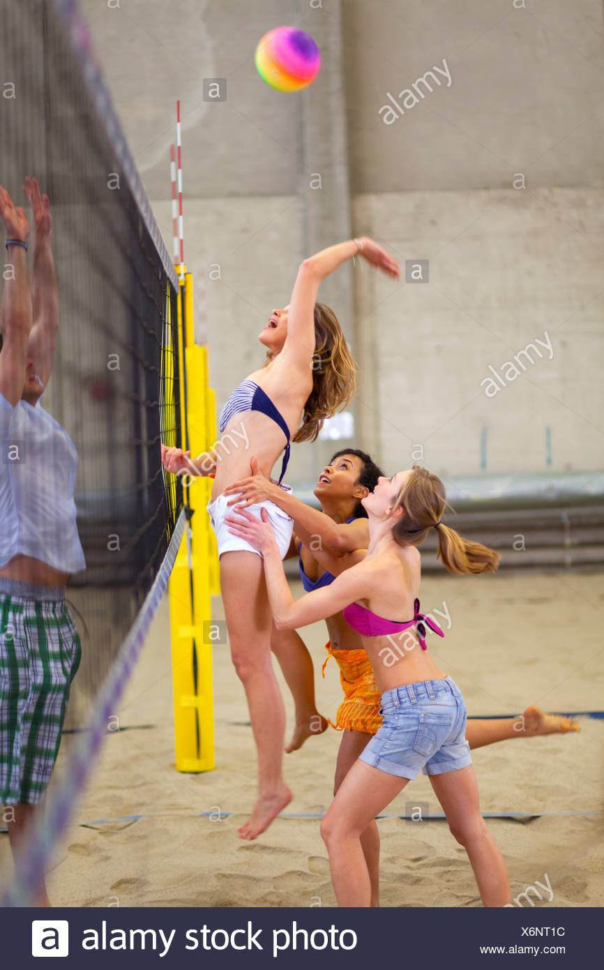 Friends playing beach volleyball at sports centre Stock Photo