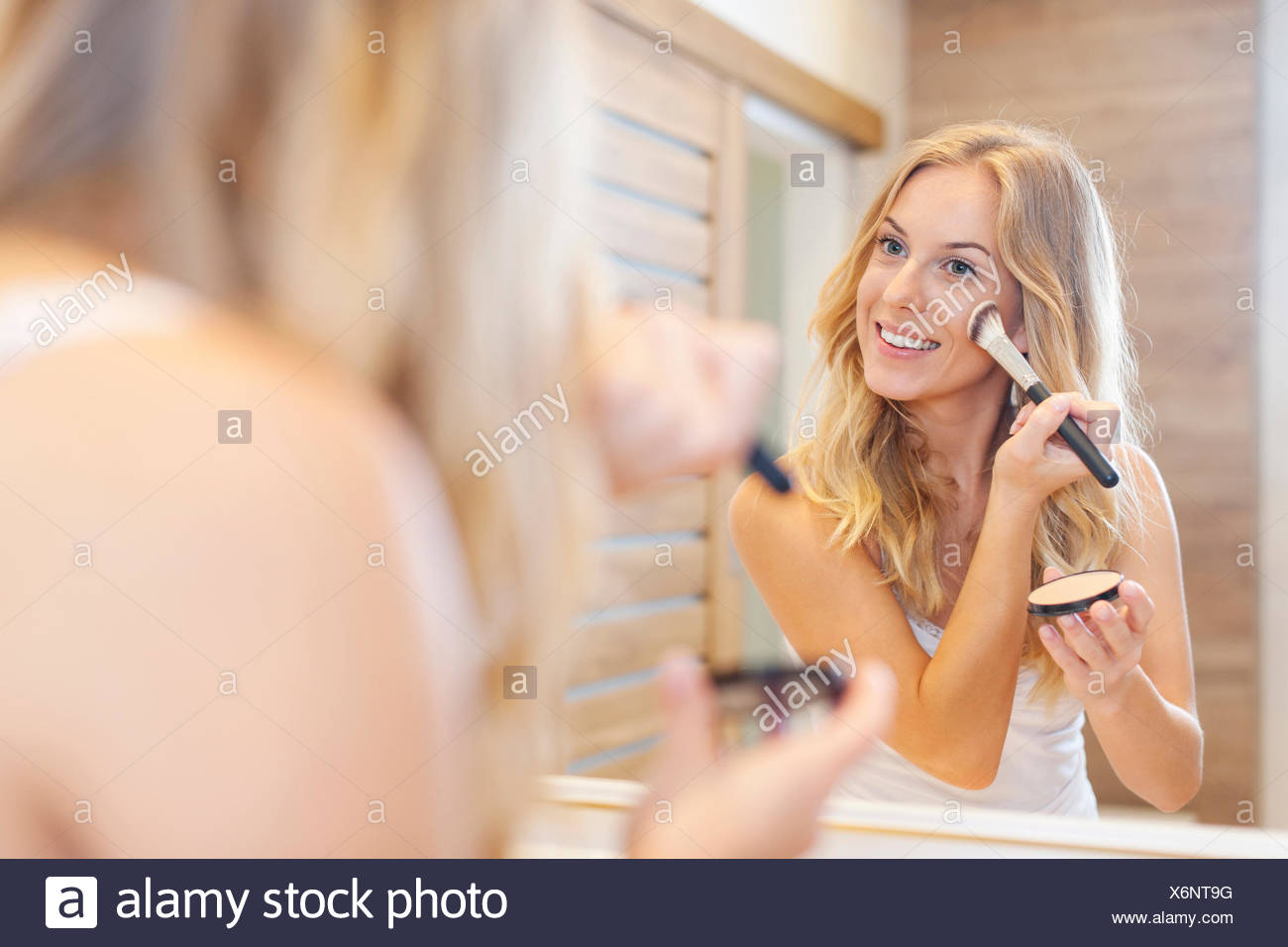 Blonde beautiful woman doing makeup in front of mirror. Debica, Poland - Stock Image