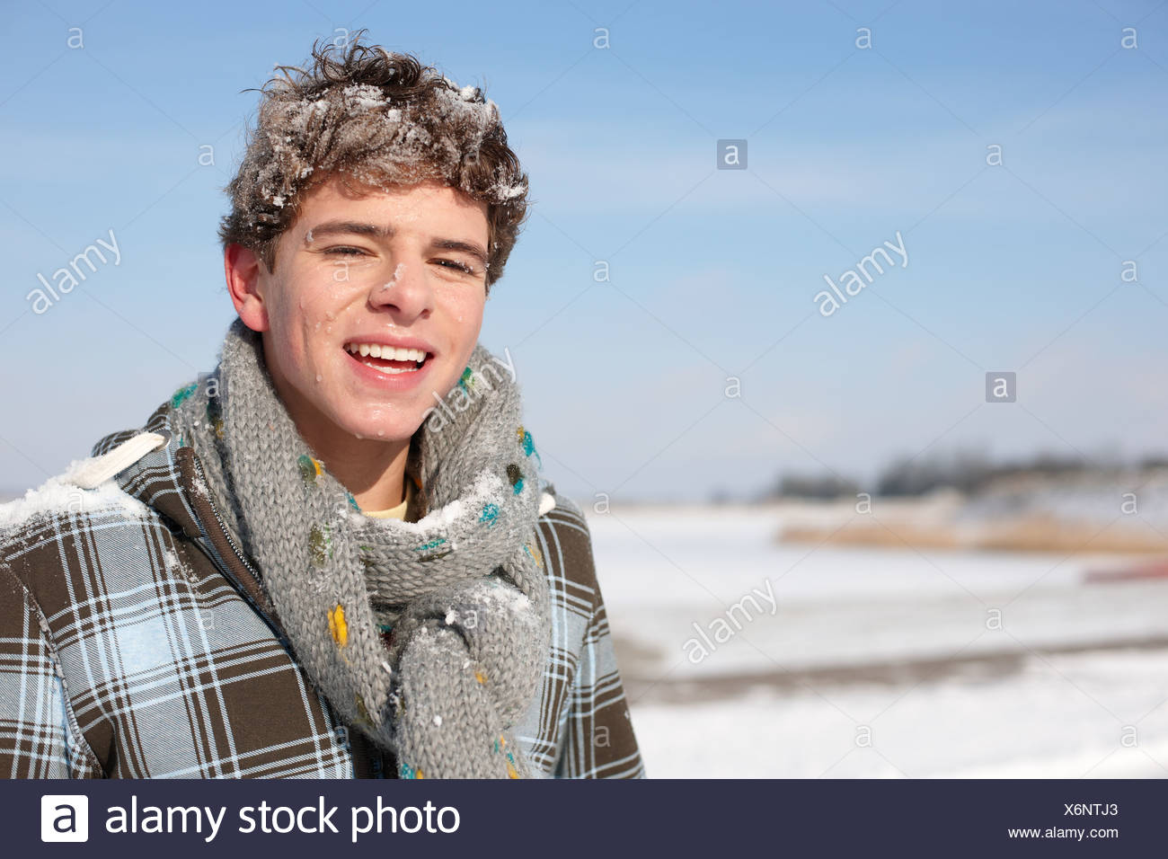 Portrait of teenage boy smiling after being hit with a snowball - Stock Image