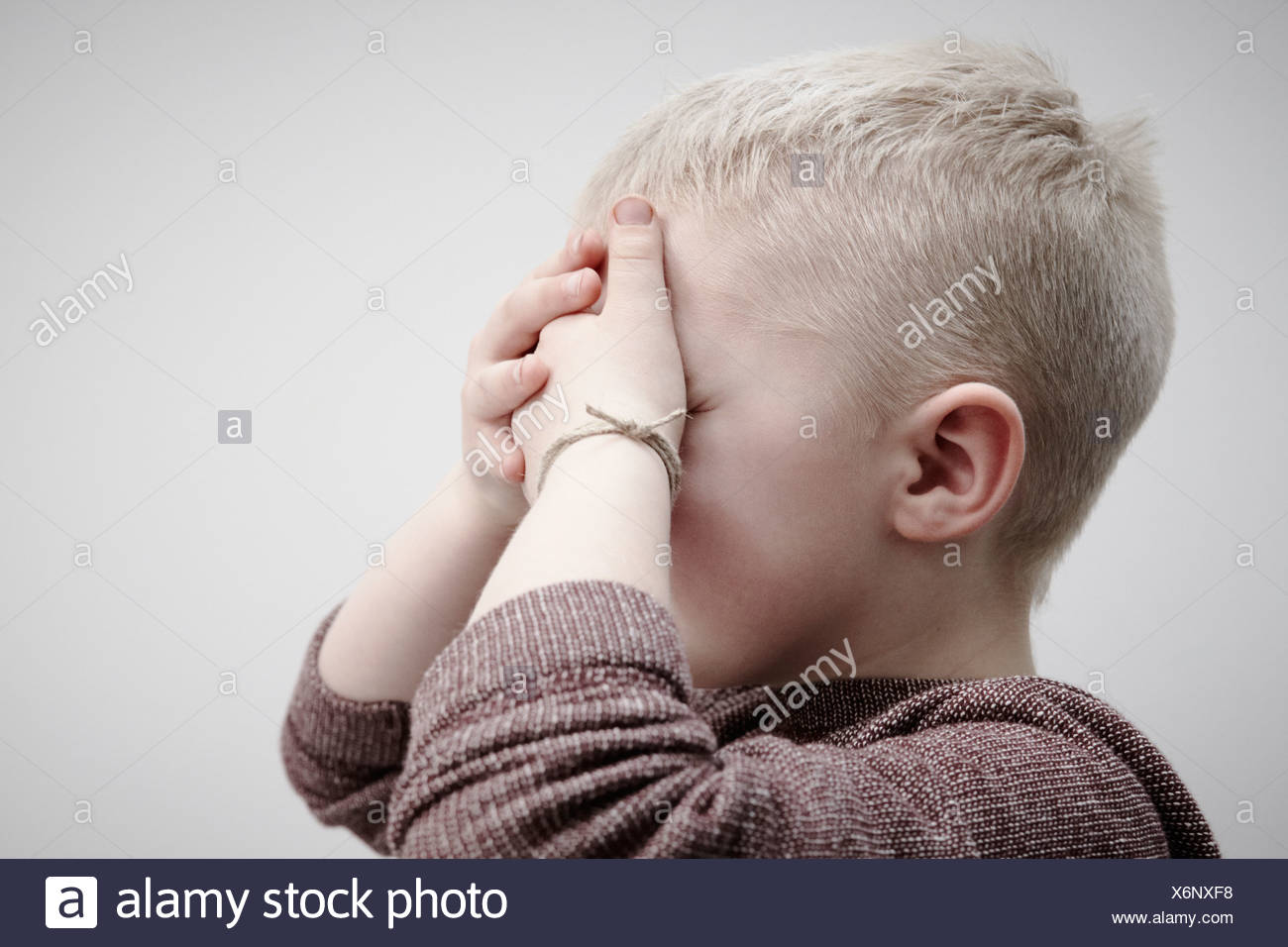 Portrait of boy wearing brown jumper, covering face with hands Stock Photo