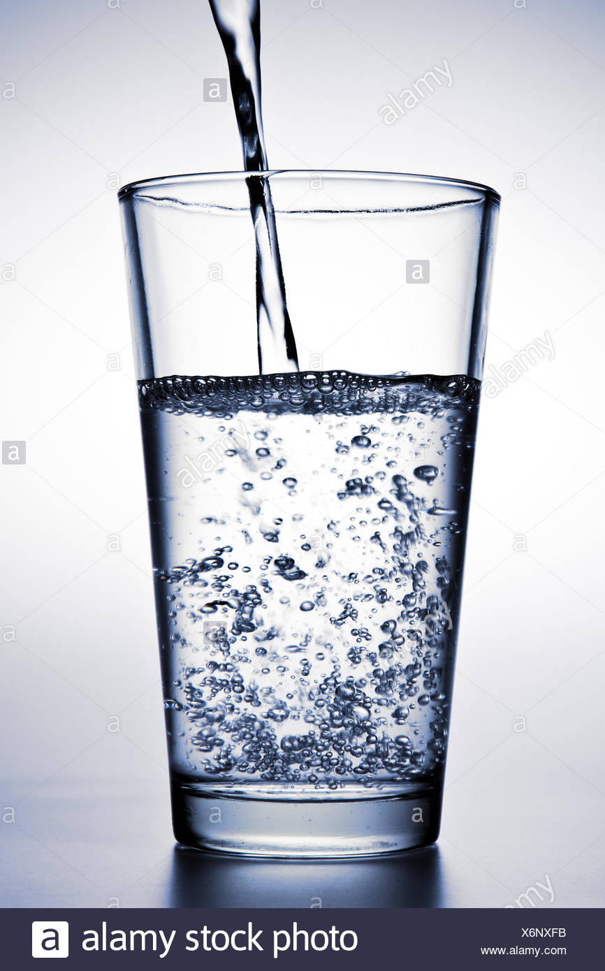 Water is being poured into a glass Stock Photo