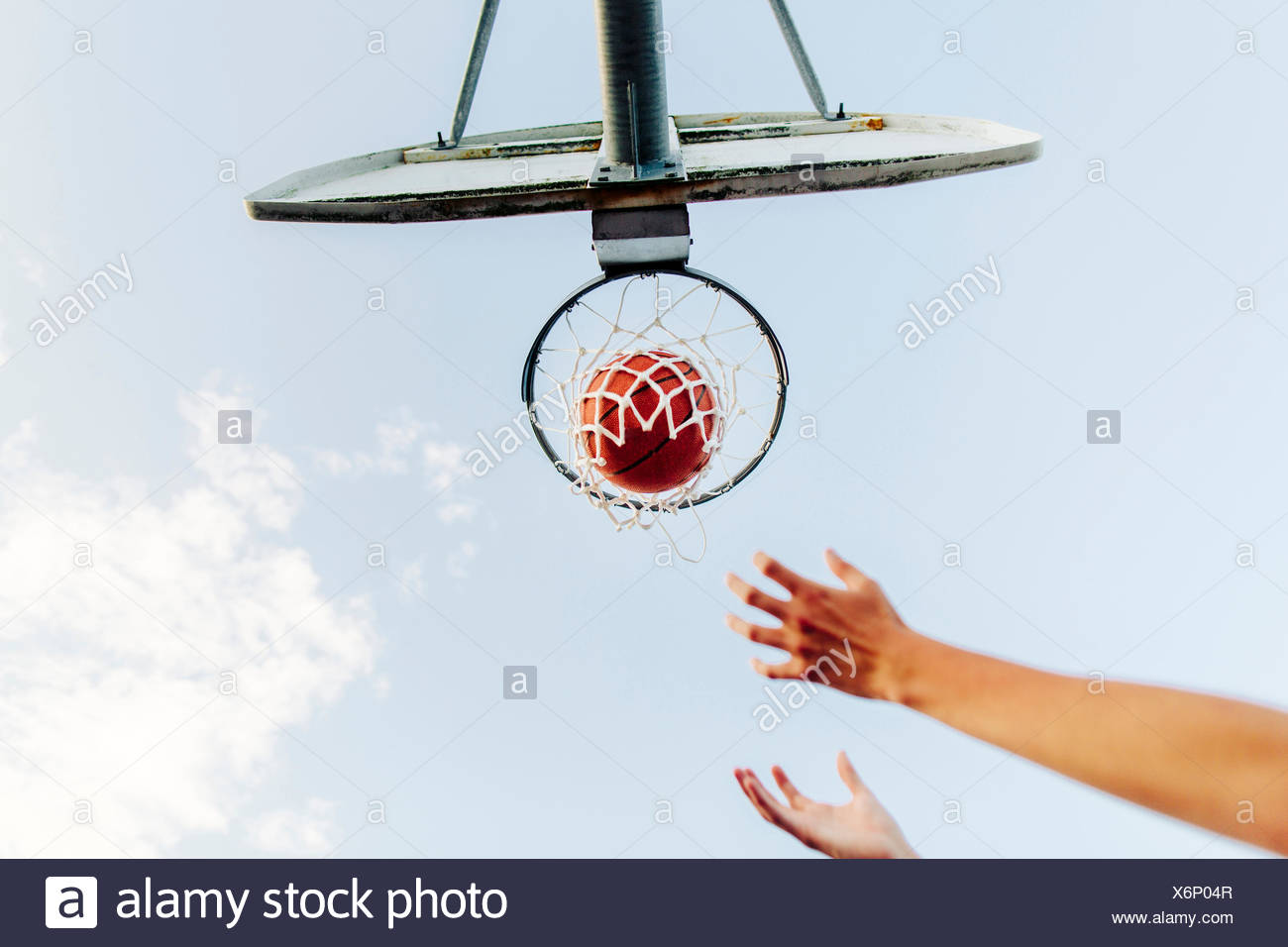 Cropped hands reaching basketball hoop against sky - Stock Image