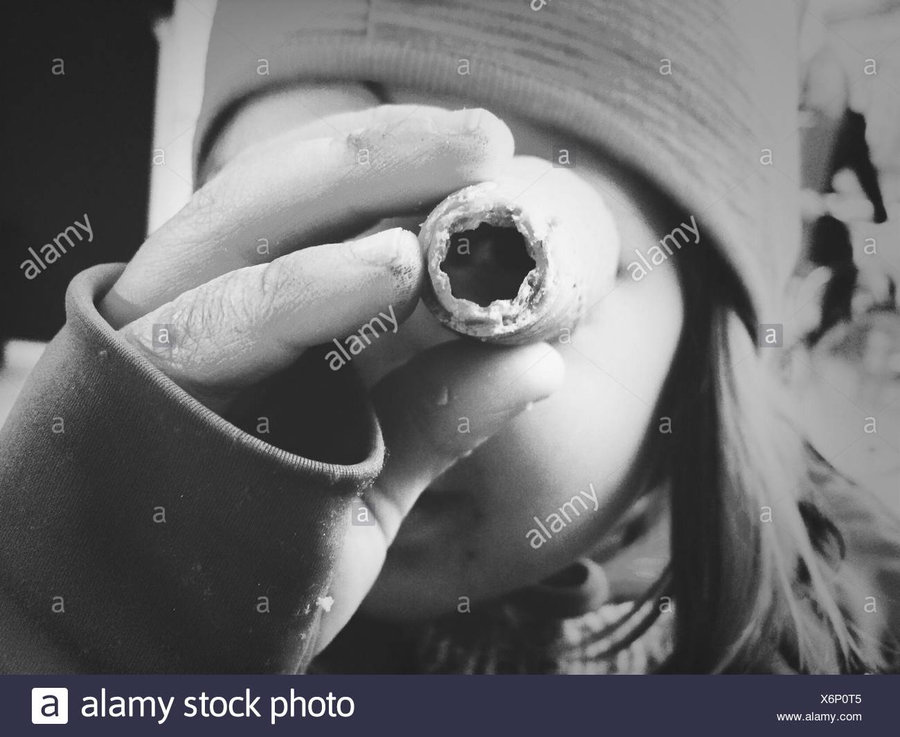 Close-Up Portrait Of Woman Looking Through An Object - Stock Image