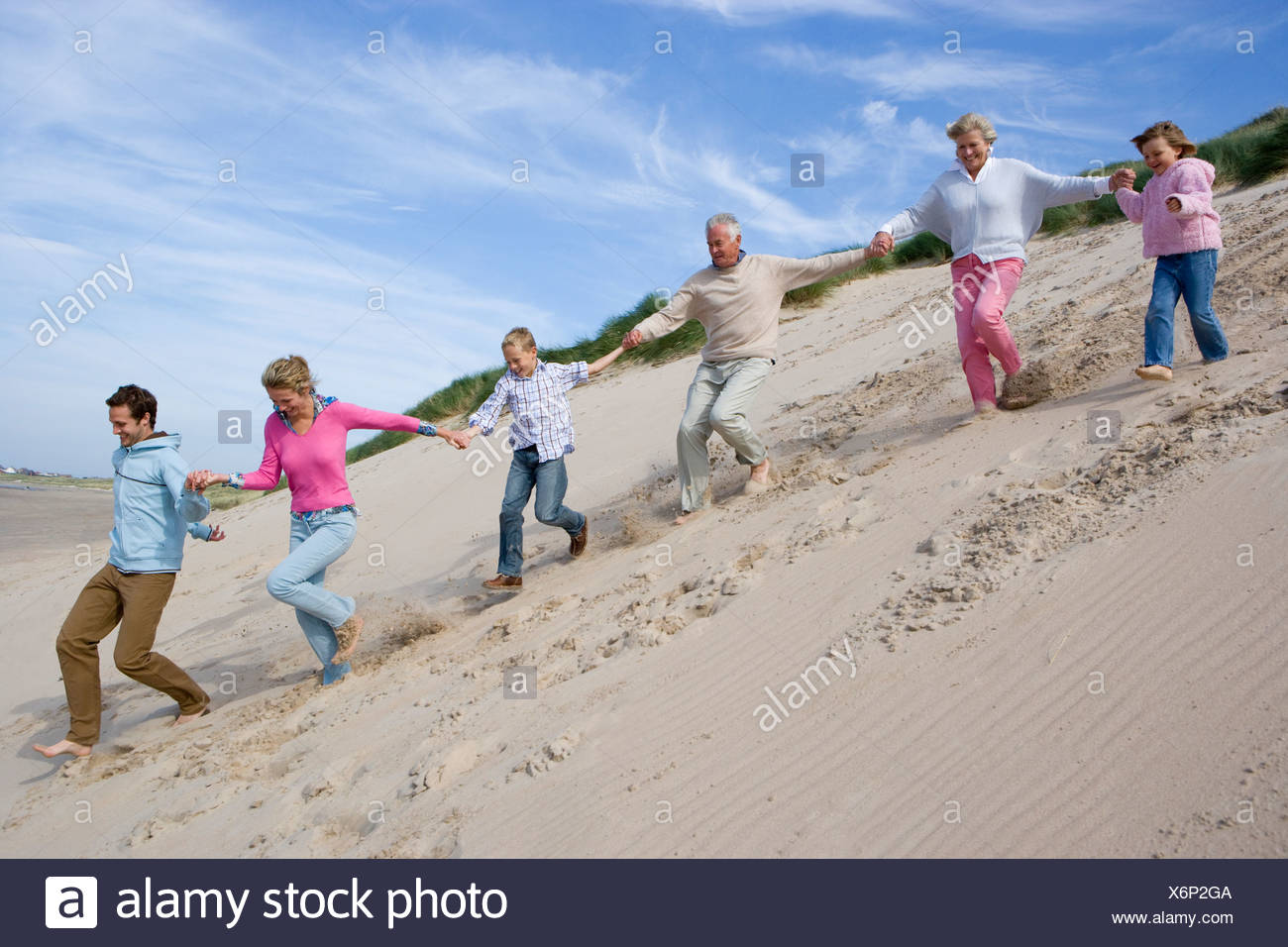 Multi generation family running down on beach - Stock Image
