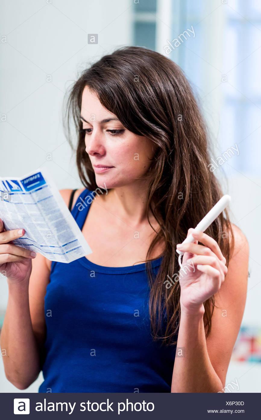 Teenage girl reading tampons instructions sheet. - Stock Image