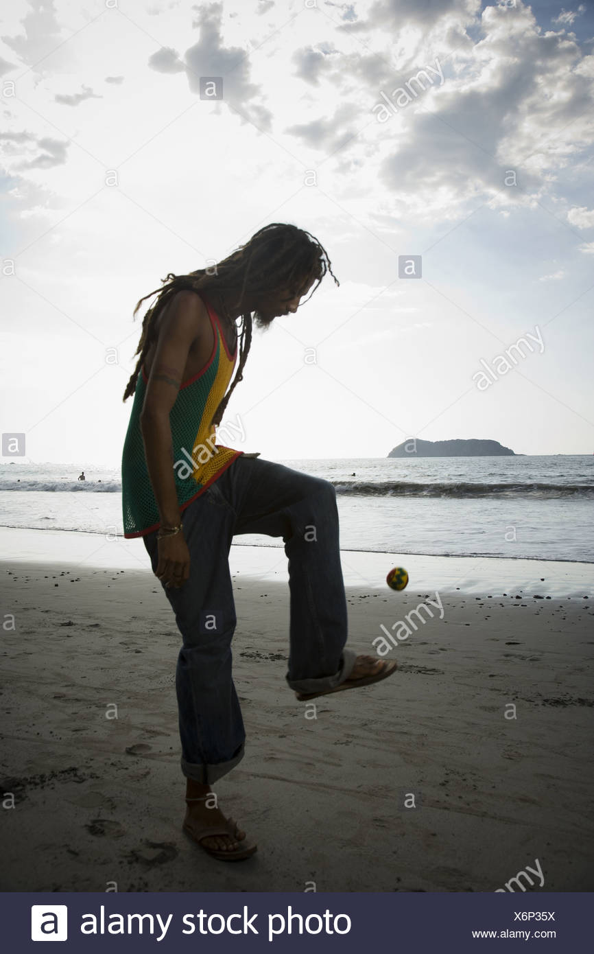 Profile of a man playing hacky sack on the beach - Stock Image
