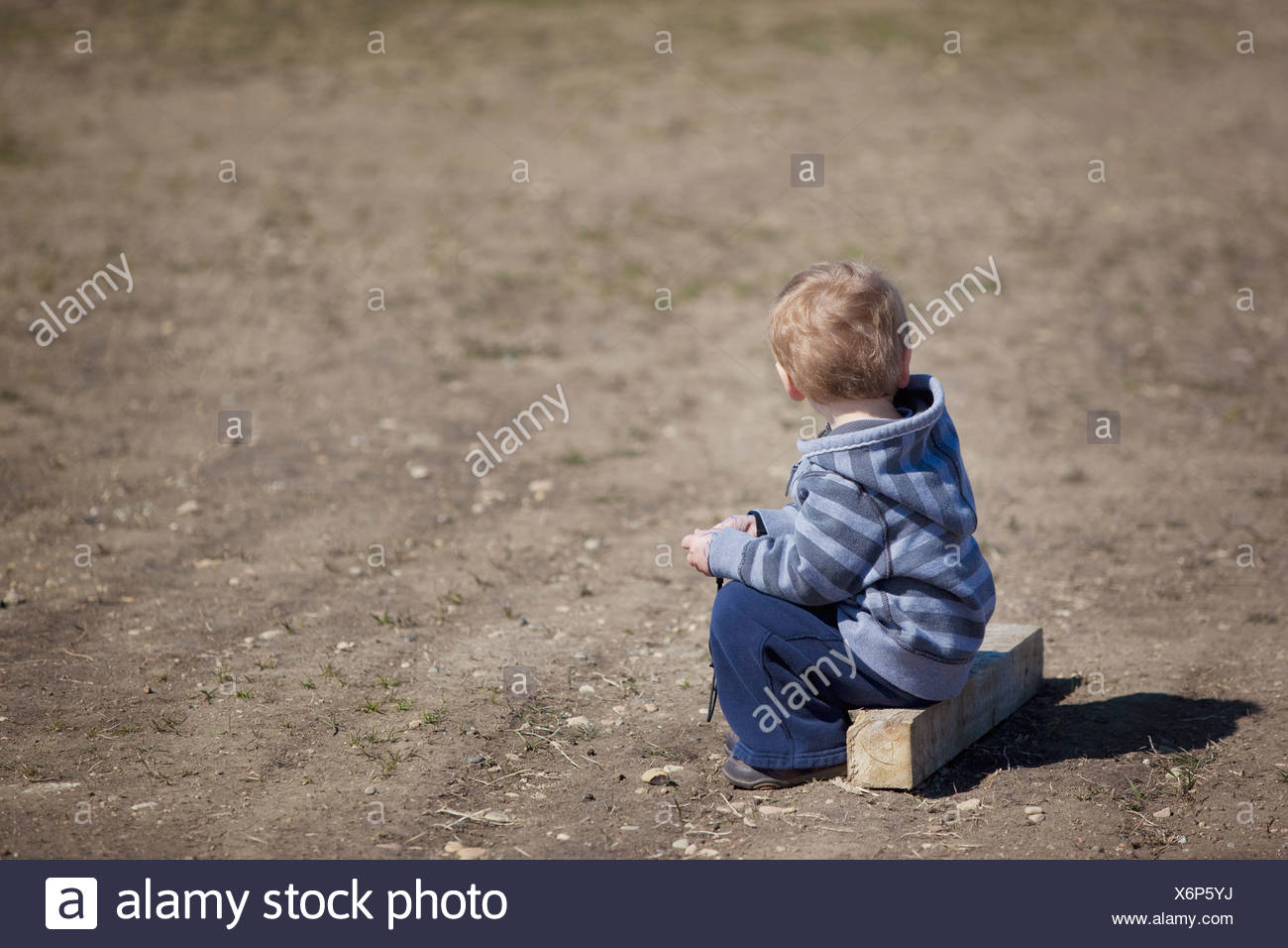 Young Boy Sitting On A Piece Of Wood - Stock Image