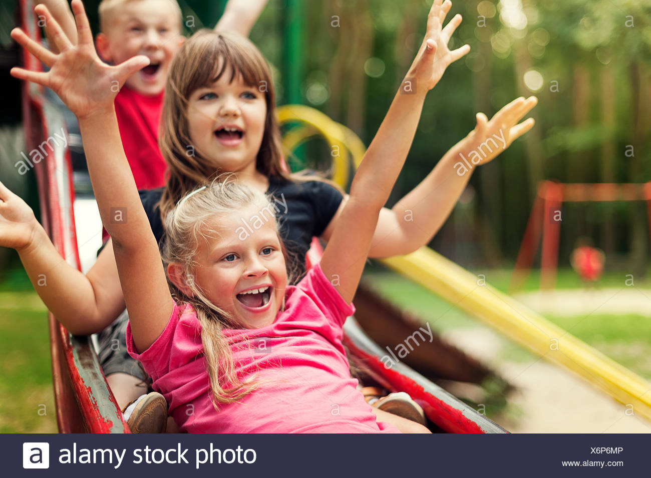 Happy kids playing on slide, Debica, Poland - Stock Image