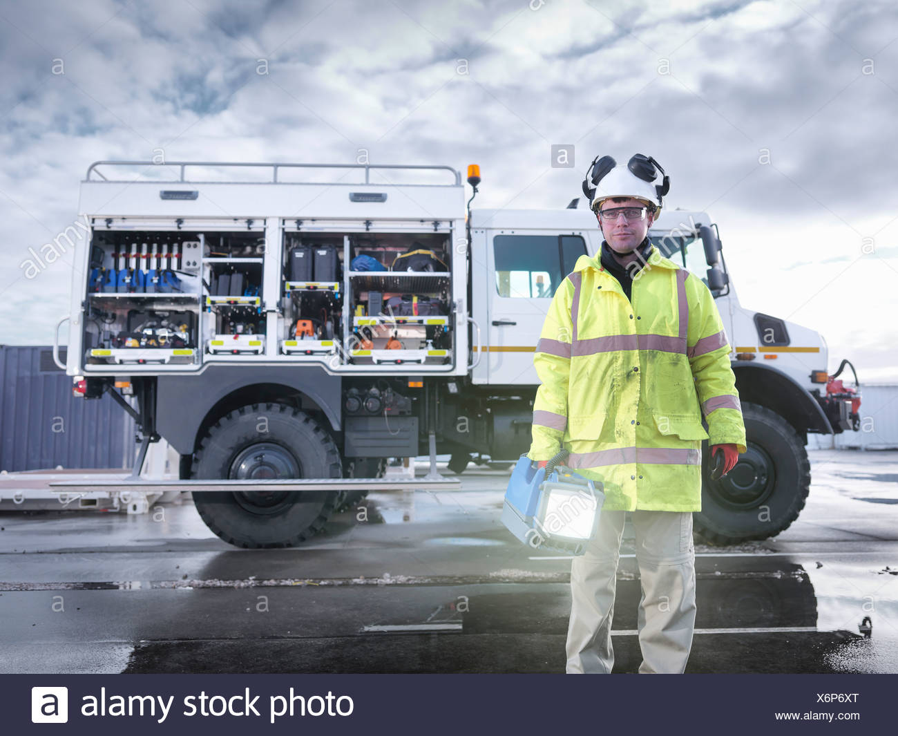 Portrait of Emergency Response worker with specialist equipment and rescue truck - Stock Image