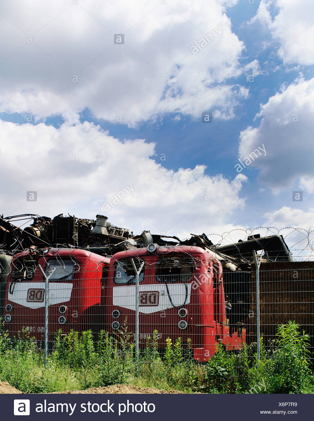 Electric locomotives in a scrapyard, behind them piled-up old metal parts - Stock Image