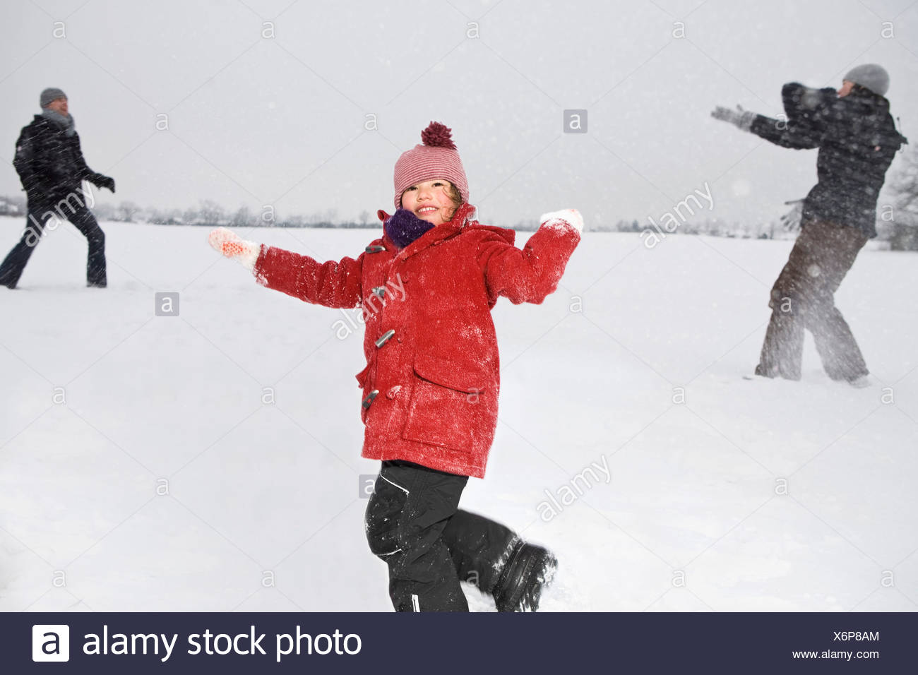 Two parents and their daughters having a snowball fight - Stock Image