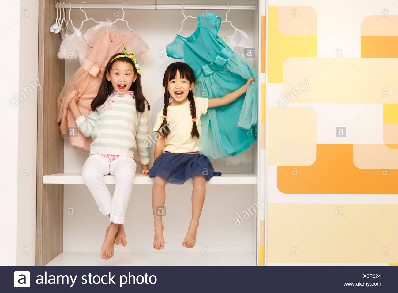 The cute little girl sitting in the closet Stock Photo