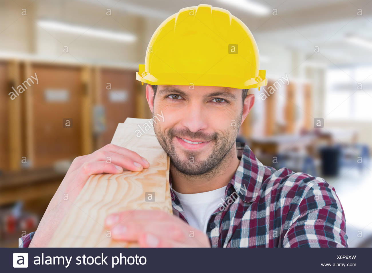 Composite image of handyman holding wood planks - Stock Image