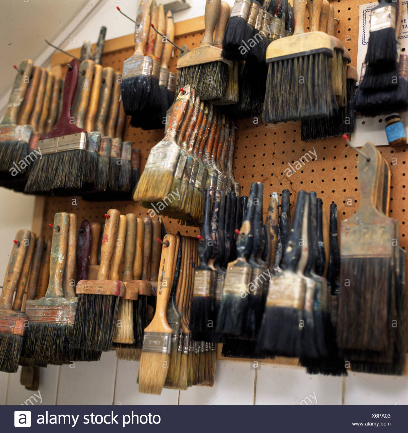 Paint brushes stored on pegboard in shed - Stock Image