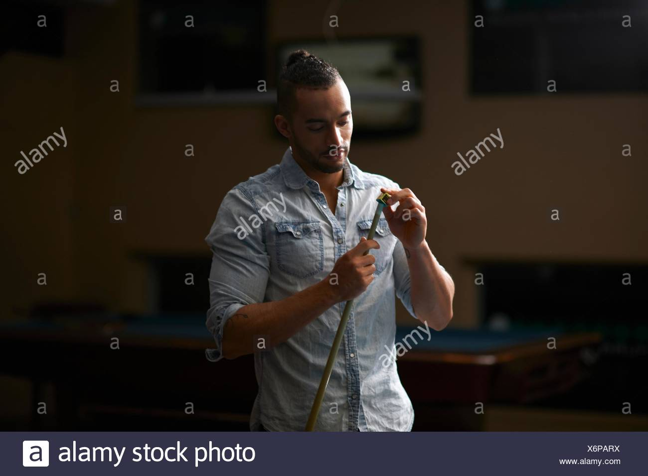 Man chalk rubbing pool cue - Stock Image