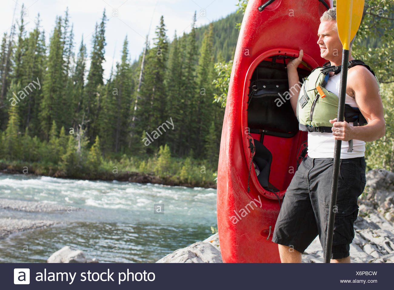 middle-aged man with kayak by waters edge - Stock Image