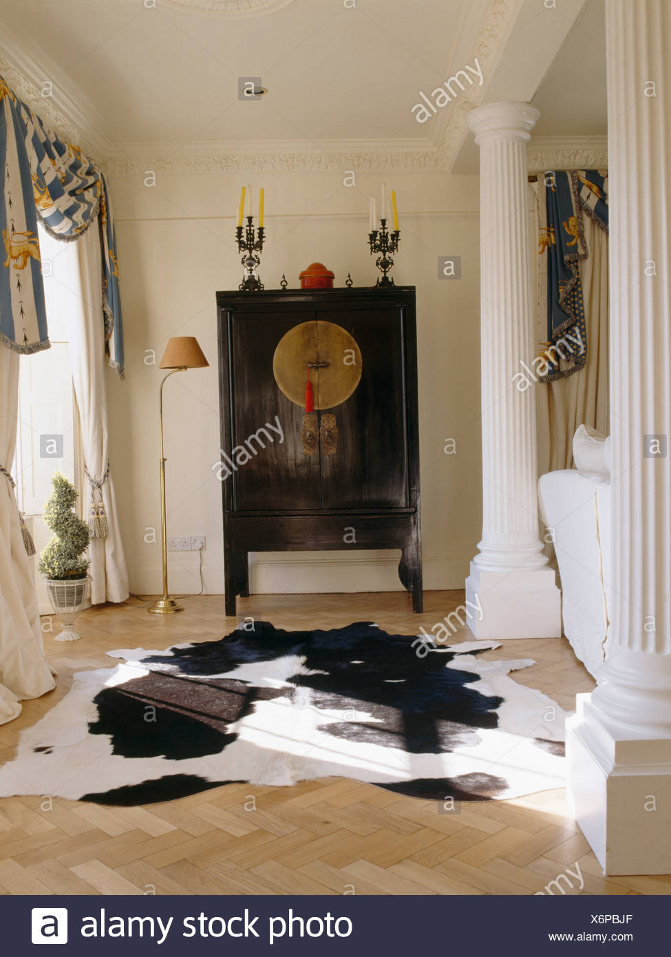 Cow-hide rug on parquet floor in country living room with ...